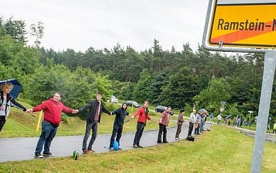 Peace activists form a human chain on the street leading towards the US air base during the 'Stopp-Ramstein' campaign in Ramstein, Germany, Saturday June 11, 2016 (Oliver Dietze/dpa via AP)
