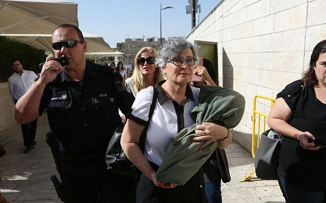 Women of the Wall Executive Director Leslie Sachs carrying a Torah scroll as she is escorted away from the Western Wall plaza by police, June 7, 2016. (Michal Fattal)