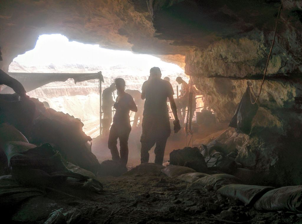 Volunteers and archaeologists working in the Cave of the Skulls, overlooking Nahal Tze'elim in the Judean Desert on June 1, 2016. (Ilan Ben Zion/Times of Israel staff)
