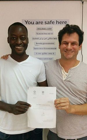 Mutasim Ali, left, and his lawyer Asaf Weitzen, with the announcement of refugee status from the Interior Ministry on June 23, 2016. (courtesy Hotline for Refugees and Migrants)