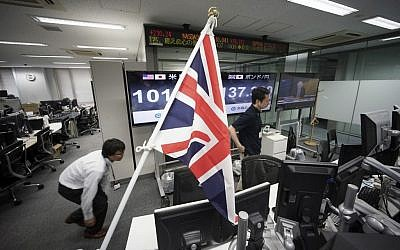 Money traders walk past a flag of the United Kingdom at a foreign exchange brokerage at a securities firm in Tokyo, Friday, June 24, 2016. (AP Photo/Eugene Hoshiko)