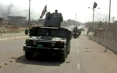 """A still image from video of Iraqi troops carrying Iraqi flags on their vehicles after a senior Iraqi commander declared that the city of Fallujah was """"fully liberated"""" from Islamic State group militants, in Fallujah, Iraq, June 26, 2016. (AP Video via AP)"""