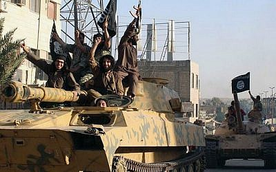 In this undated file image posted by the Raqqa Media Center in Islamic State-held territory, on Monday, June 30, 2014, IS fighters ride tanks during a parade in Raqqa, Syria. (AP Photo/Raqqa Media Center, File)