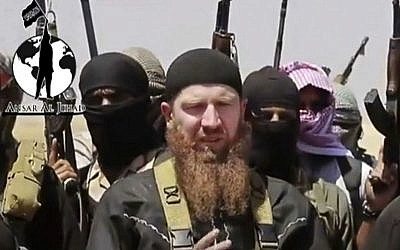 This file image made from undated video posted during the weekend of June 28, 2014 on a social media account frequently used for communications by the Islamic State shows Omar al-Shishani standing next to the group's spokesman among a group of fighters as they declare the elimination of the border between Iraq and Syria. (AP Photo/militant social media account via AP video)