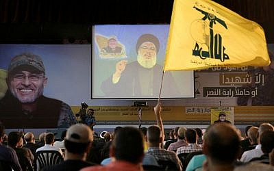 A Hezbollah supporter waves his group's flag, as Hezbollah leader Hassan Nasrallah, center, speaks via a video link, in the southern suburb of Beirut, Lebanon, Friday, June 24, 2016.  (AP Photo/Hussein Malla)