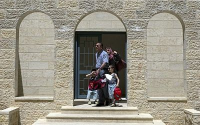 In this June 4, 2016 photo, a Palestinian family leaves their newly delivered apartment in the West Bank city of Rawabi, north of Ramallah. (AP Photo/Nasser Nasser)