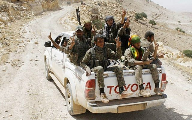 Kurdish fighters of the YPG flash victory signs as they sit on their pickup on their way to battle against the Islamic State, near Kezwan mountain, northeast Syria, May 20, 2015. (The Kurdish fighters of the People's Protection Units via AP/File)