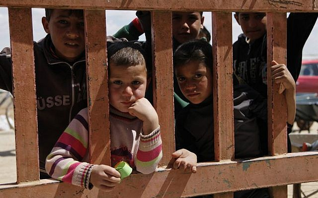 Syrian refugees look through the gate of a grocery store at the al-Azraq refugee camp in northeast Jordan, April 14, 2016. (AP Photo/ Sam McNeil)