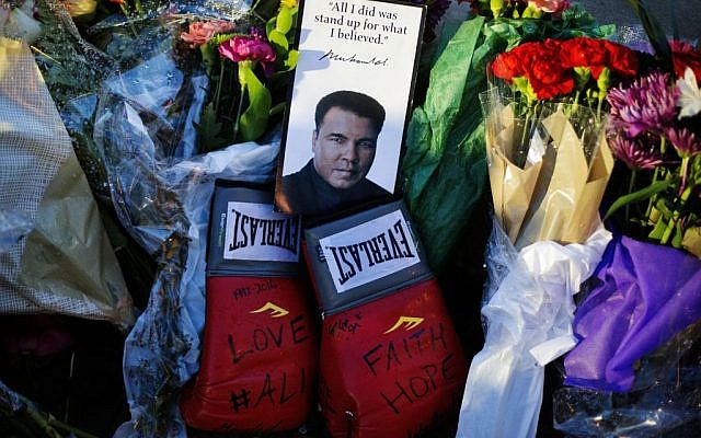 Boxing gloves and a message sit among flowers at a makeshift memorial to Muhammad Ali at the Muhammad Ali Center in Louisville, Kentucky, June 4, 2016. (AP/David Goldman)