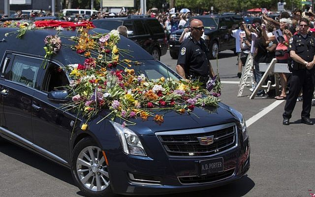 Flowers pile up on the hearse carrying Muhammad Ali spectators watch his funeral procession enter Cave Hill Cemetery, Friday, June 10, 2016, in Louisville, Ky. (John Minchillo/AP)