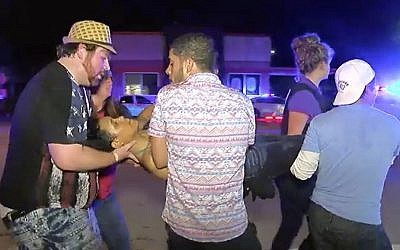 An injured person is escorted out of the Pulse nightclub after a shooting rampage, Sunday morning June 12, 2016, in Orlando, Fla. (AP/Steven Fernandez)