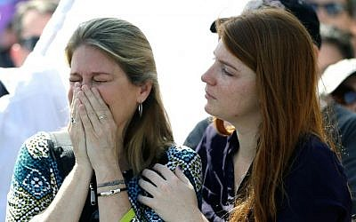 Randa Black, left, cries and is comforted by McKenna Post after seeing demonstrators across the street during a rally to show support and solidarity near the funeral service for Christopher Andrew Leinonen, one of the victims of the Pulse nightclub mass shooting, outside the Cathedral Church of St. Luke, Saturday, June 18, 2016, in Orlando, Florida. (AP Photo/John Raoux)