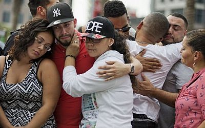 Mourners console each other as they grieve the loss of their friends Amanda Alvear and Mercedez Flores who were killed in the mass shooting at the Pulse nightclub, as they visit a makeshift memorial downtown, Monday, June 13, 2016, in Orlando, Fla. (AP Photo/David Goldman)