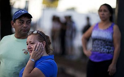 Carmen Feldman, of Orlando, right, cries while visiting for the first the scene of the Pulse nightclub mass shooting from a block away with Jose Garcia, left, Friday, June 17, 2016, in Orlando, Fla. (AP/David Goldman)