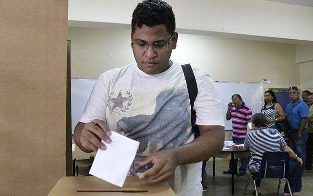 Puerto Rico resident Hector Feliciano votes during the US territory's Democratic primary election at the Luis Llorens Torres Elementary School in San Juan, Puerto Rico, Sunday June 5, 2016 . (AP Photo/Carlos Giusti)