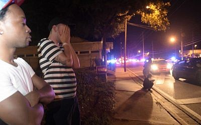 Jermaine Towns, left, and Brandon Shuford wait down the street from a multiple shooting at a nightclub in Orlando, Fla., Sunday, June 12, 2016. (AP Photo/Phelan M. Ebenhack)