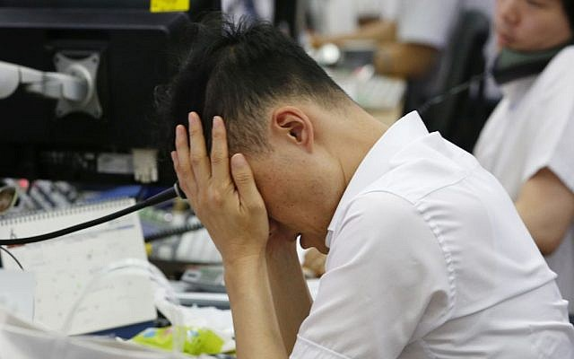 A currency trader rubs his eyes at the foreign exchange dealing room in Seoul, South Korea, Friday, June 24, 2016. (AP/Lee Jin-man)