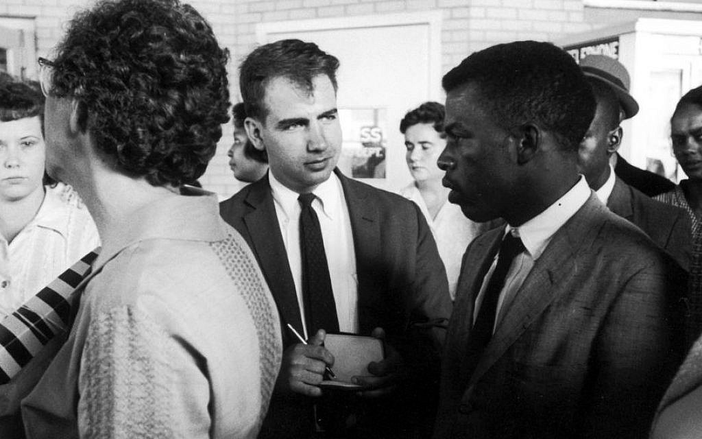 Writer Calvin Trillin, center, interviewing John Lewis in Birmingham, Alabama, as the Freedom Riders were boarding the bus for Montgomery in 1961. (LIFE Images Collection/via JTA)