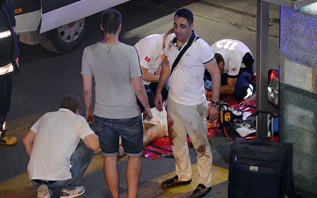 Turkish rescue services help a wounded person outside Ataturk Airport in Istanbul, Tuesday, June 28, 2016. (Ismail Coskun, IHA via AP)
