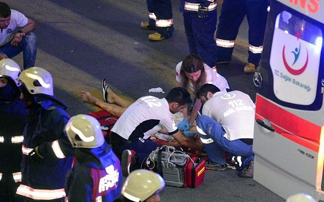 Turkish rescue services members help a wounded person outside Istanbul's Ataturk airport, Tuesday, June 28, 2016. (Ismail Coskun/IHA via AP)