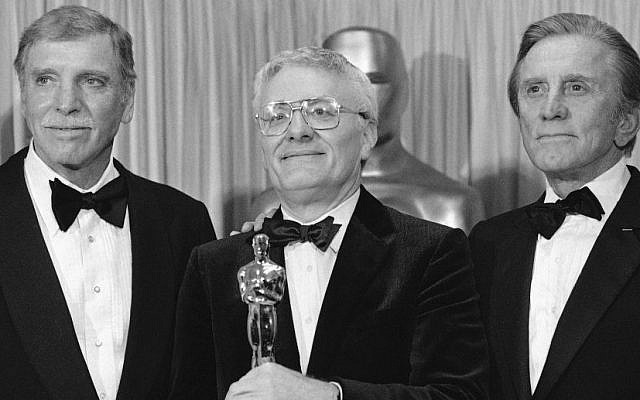 """Actors Burt Lancaster, left, and Kirk Douglas, right, stand with Peter Shaffer, winner of the best adapted screenplay Oscar for """"Amadeus"""", during the Academy Awards in Los Angeles, Ca., USA, March 25, 1985. (AP Photo, FILE)"""