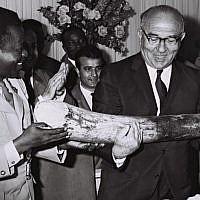 Congolese premier Gen. Leonard Mulamba gives Prime Minister Levi Eshkol an elephant tusk in a ceremony outside Kinshasa, June, 1966. (Moshe Fridan/GPO)