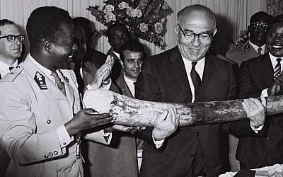 Congolese premier Gen. Leonard Mulamba gives Prime Minister Levi Eshkol an elephant tusk in a ceremony outside Kinshasa June 1966