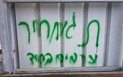 Graffiti reading 'Arabs out' and 'price tag' is sprayed on a wall in the Arab town of Abu Ghosh, near Jerusalem, on June 9, 2016 (photo credit: Israel Police)