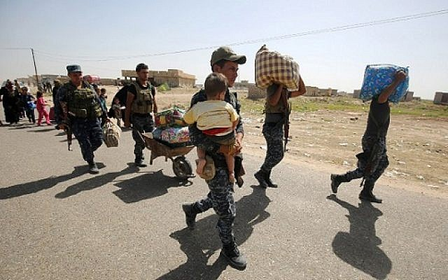 Members of the Iraqi government forces help people reach a military point as they flee the violence in their village of Saqlawiyah, north west of Fallujah, on June 3, 2016.  / AFP PHOTO / AHMAD AL-RUBAYE