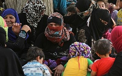 Displaced Iraqis, who fled the al-Falahat village west of Fallujah due to fighting between Iraqi government forces and the Islamic State (IS) group, wait to receive food and aid at the village of al-Azraqiyah, on June 4, 2016. AFP PHOTO / AHMAD AL-RUBAYE