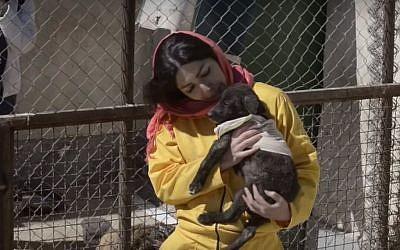 A woman holds a dog at an Iranian dog shelter (YouTube screenshot)
