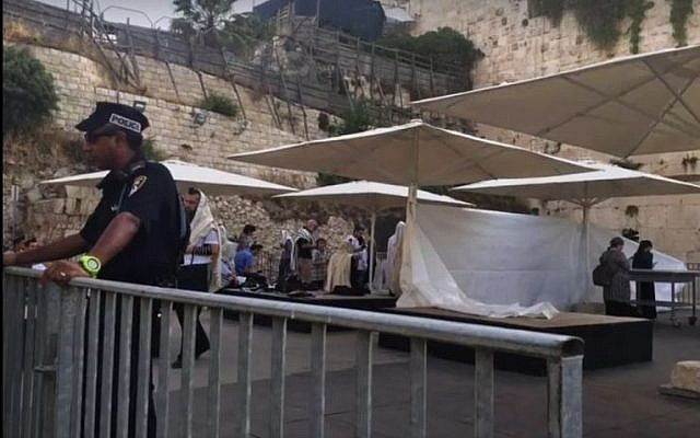 A police officer stands in front of a makeshift partition erected ahead of an Orthodox prayer service at the mixed gender Western Wall plaza on June 14, 2016. screen capture: Facebook)