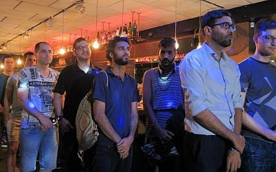People observe a minute of silence in honor of the victims of the Orlando massacre in a vigil at Tel Aviv's Evita Bar on June 14, 2016. (Melanie Lidman/Times of Israel)