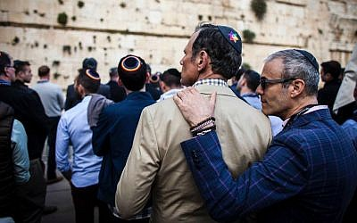 Jonathan Ringel, from New York City, rests his head on the shoulder of Cary Brown, his partner of five years  during a Shabbat eve ceremony at the Western Wall, May 27, 2016. (Courtesy)