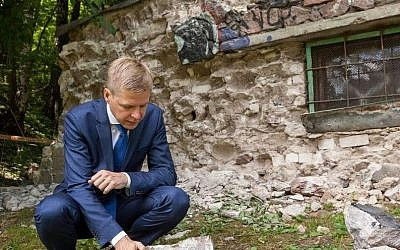 Vilnius Mayor Remigijus Šimašius dismantling a generator station built from Jewish headstones on the Lithuanian capital's Olandu Street on June 22, 2016. (Courtesy of the municipality of Vilnius)
