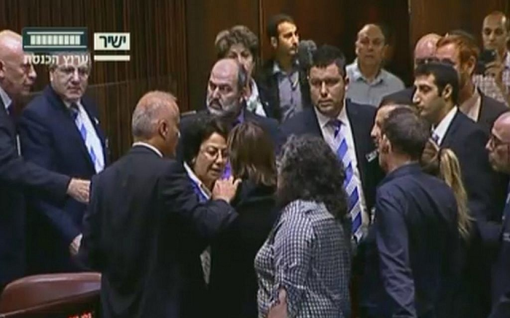 Joint (Arab) List MK Hanin Zoabi, center, confronted by fellow lawmakers in the Knesset plenum over her comments on the Israel-Turkey reconciliation agreement on June 29, 2016 (screen capture: Knesset Channel)
