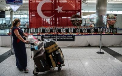 Two days after a triple suicide bombing, a passenger looks at the pictures of killed airport employees at Ataturk airport international terminal in Istanbul on June 30, 2016. (AFP/OZAN KOSE/)