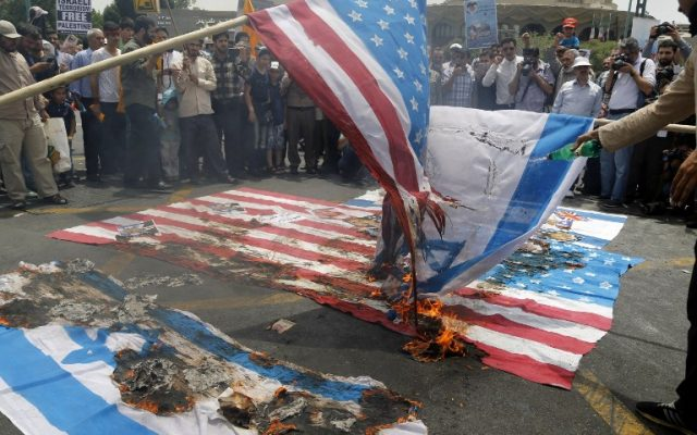 Illustrative. Iranian protestors set US and Israeli flags afire during a parade marking al-Quds (Jerusalem) Day in Tehran on July 1, 2016. (AFP/Atta Kenare)