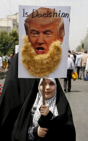 "An Iranian girl holds up a portrait of US Republican presidential candidate Donald Trump adorned with jihadist-style beard and a slogan reading ""is Daeishian"" (Daesh is Arabic acronym for Islamic State), during a parade marking al-Quds (Jerusalem) Day in Tehran on July 01, 2016. (Atta Kenare/AFP)"