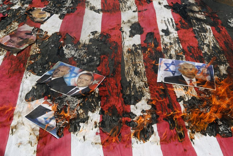Portraits of Bahraini King Hamad (top L), Prime Minister Benjamin Netanyahu and Turkish President Recep Tayyip Erdogan lie on a US flag in flames during a parade marking al-Quds (Jerusalem) Day in Tehran on July 01, 2016. (Atta Kenare/AFP)