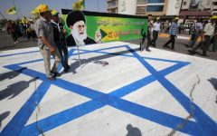 Illustrative: Iraqi men stand on an Israeli flag and hold a banner depicting Iran's Supreme Leader Ayatollah Ali Khamenei as they take part in a parade marking al-Quds (Jerusalem) Day in Baghdad, July 1, 2016. (AFP Photo/Ahmad Al-Rubaye)