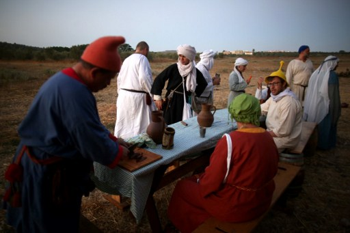 Members of a reenactment group, dressed in medieval costumes, with author (in yellow Jew's cap) at the camp near Tzippori on June 30, 2016. (AFP PHOTO / MENAHEM KAHANA)