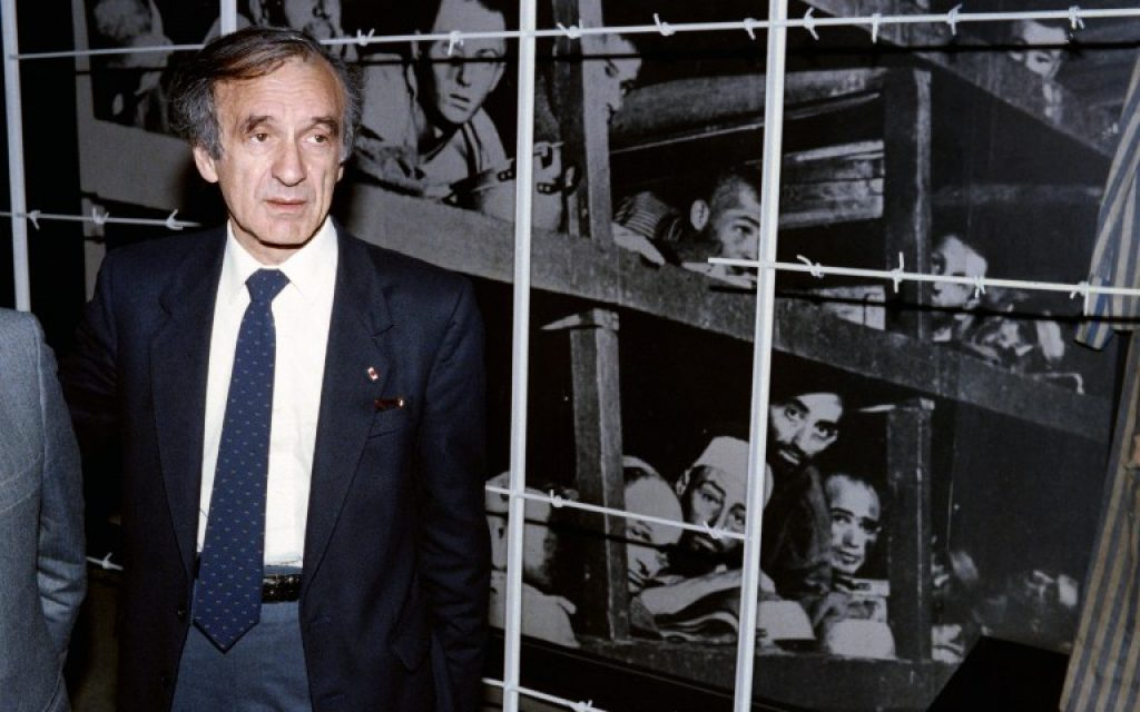 This December 18, 1986, file photo shows Nobel Peace prize winner and writer Elie Wiesel standing in front of a photo of himself (bottom 3rd from R) and other inmates, taken at the Buchenwald concentration camp in 1945, during his visit to the Holocaust Memorial Center Yad Vashem in Jerusalem. (AFP/ SVEN NACKSTRAND)