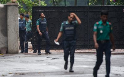 Bangladeshi policemen exit from a gate leading to an upscale cafe in Dhaka on July 3, 2016 a day after a bloody siege ended with the death of 20 foreign hostages. (AFP/ROBERTO SCHMIDT)