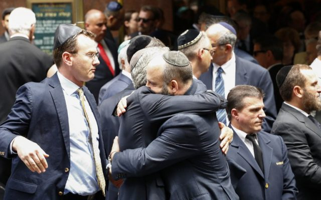 People embrace outside the Fifth Avenue Synagogue during the funeral for Nobel laureate and Holocaust survivor Elie Wiesel on July 3, 2016 in New York. (AFP PHOTO / KENA BETANCUR)