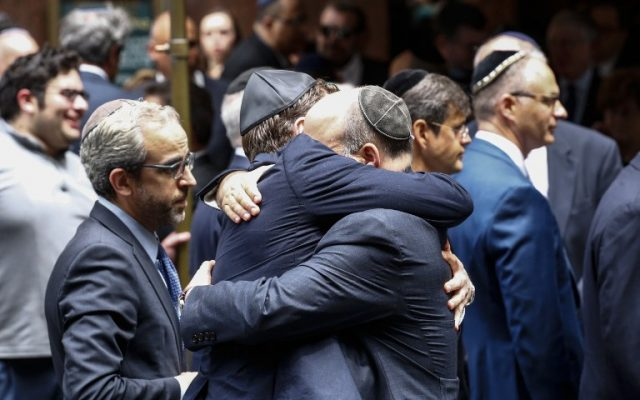 People embrace outside the Fifth Avenue Synagogue during the funeral for Nobel laureate and Holocaust survivor Elie Wiesel on on July 3, 2016 in New York. (AFP PHOTO / KENA BETANCUR)