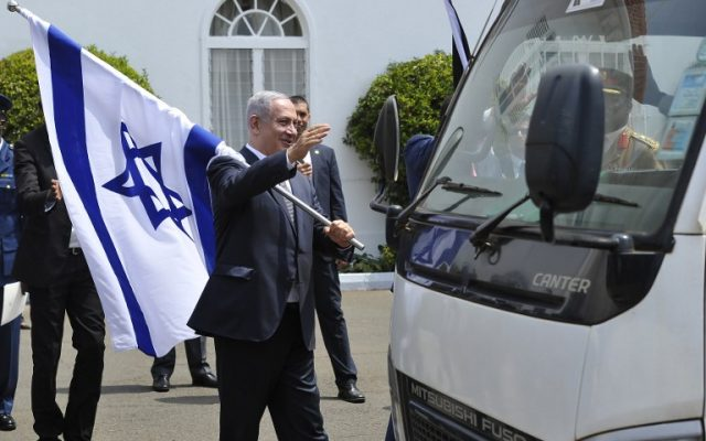 Benjamin Netanyahu holds an Israeli flag after a joint press conference with Kenya's President on July 5, 2016 at the State House, in Nairobi. (AFP/SIMON MAINA)