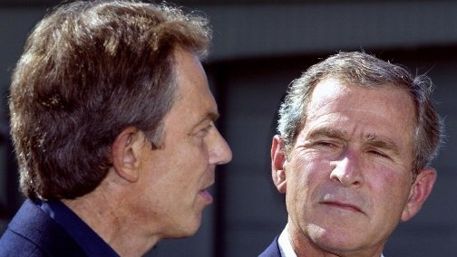 Then-President George W. Bush looking at then-British Prime Minister Tony Blair as they deliver statements to the media after Blair's arrival at the US presidential retreat, Camp David, Maryland, September 7, 2002. (AFP/Paul J. Richards)