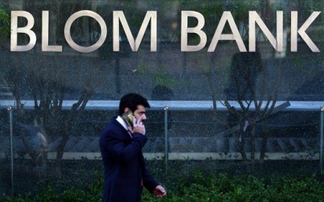 This file photo taken on June 13, 2016 shows a man walking past the sign of the BLOM BANK in the Lebanese capital Beirut. (AFP PHOTO / PATRICK BAZ)