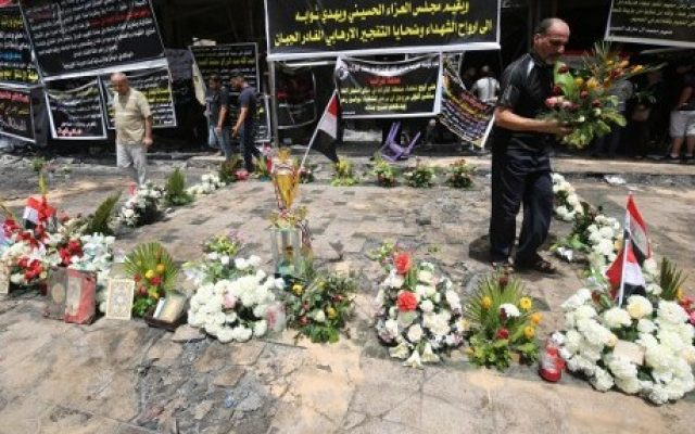 Iraqis lay flowers on July 6, 2016, at the site of a suicide bombing that ripped through Baghdad's busy shopping district of Karrada on July 3. (AFP / Ahmad al-Rubaye)